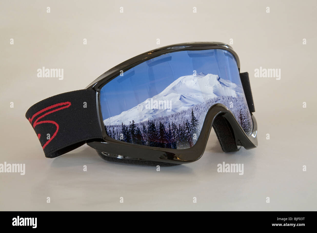 Ski goggles with the reflection of a snow capped peak in them - Stock Image