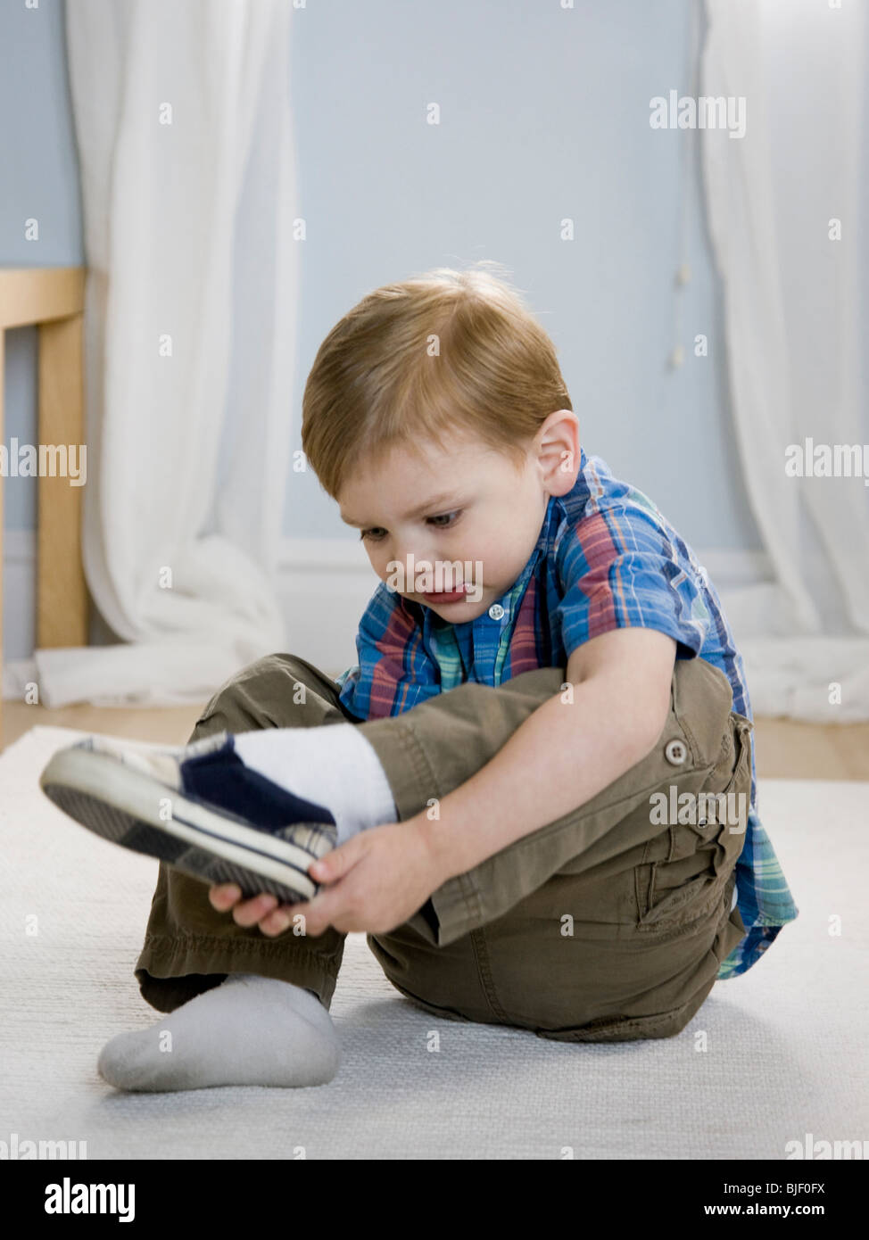 Little Boy Putting On Shoes Stock Photo: 28603902