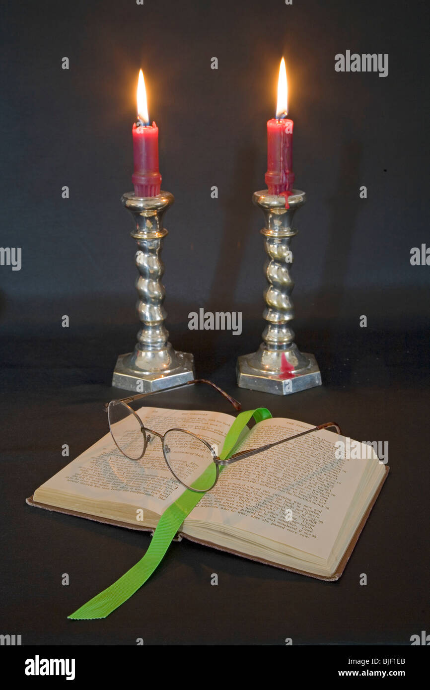 Lighted candles, reading glasses, and a good book. - Stock Image