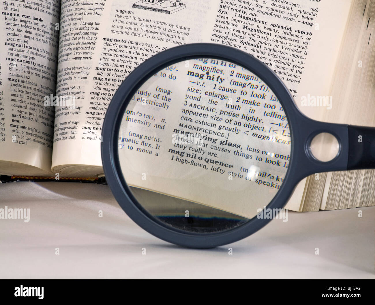 A magnifying glass over the word magnify in an English Dictionary - Stock Image