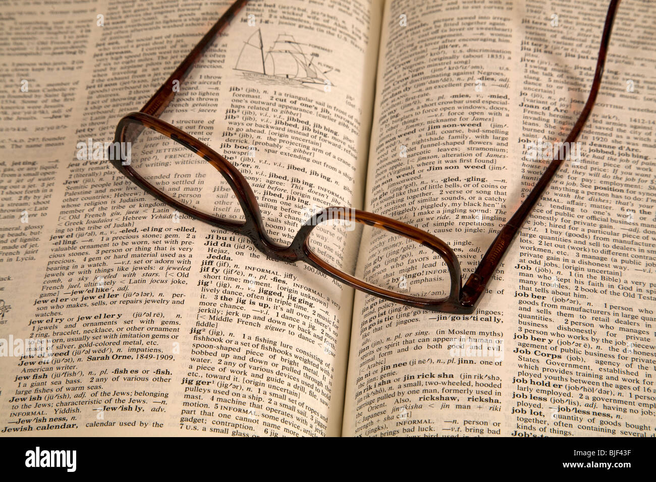 Reading glasses on an English dictionary - Stock Image