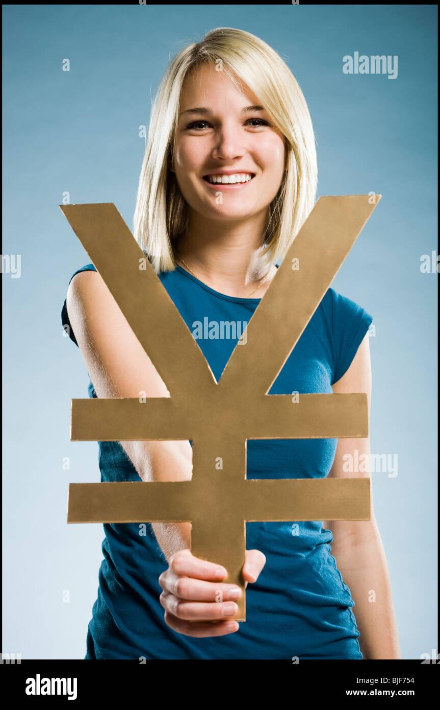woman holding up a yen symbol - Stock Image