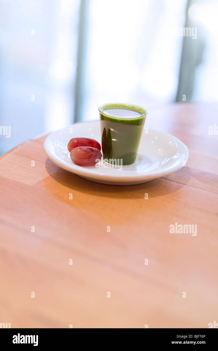 Fresh shot of Wheatgrass in a saucer with two red grapes on the side on a wooden surface - Stock Image