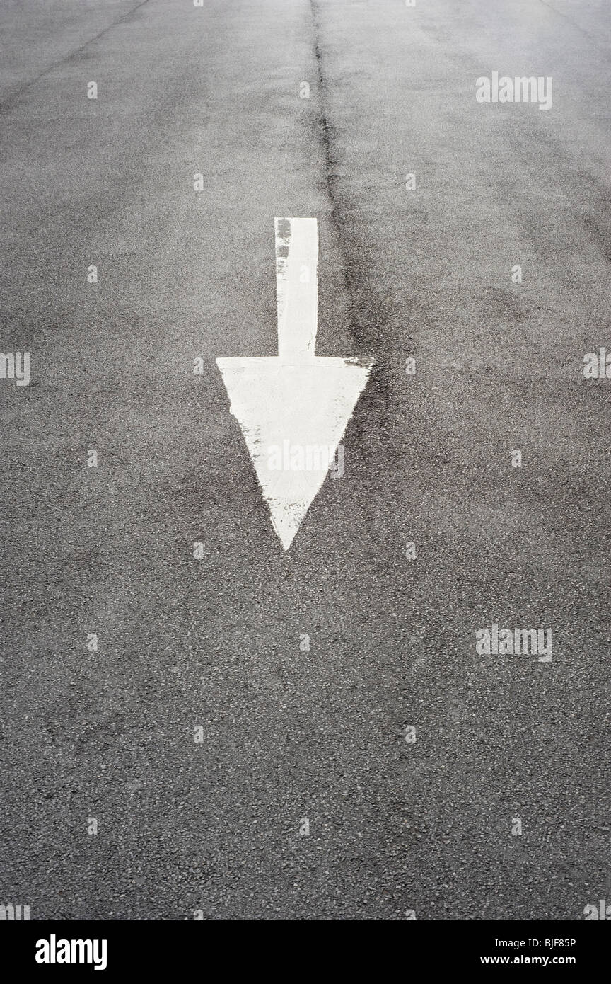 Arrow Pointing Down painted on a Tarmac road - Stock Image