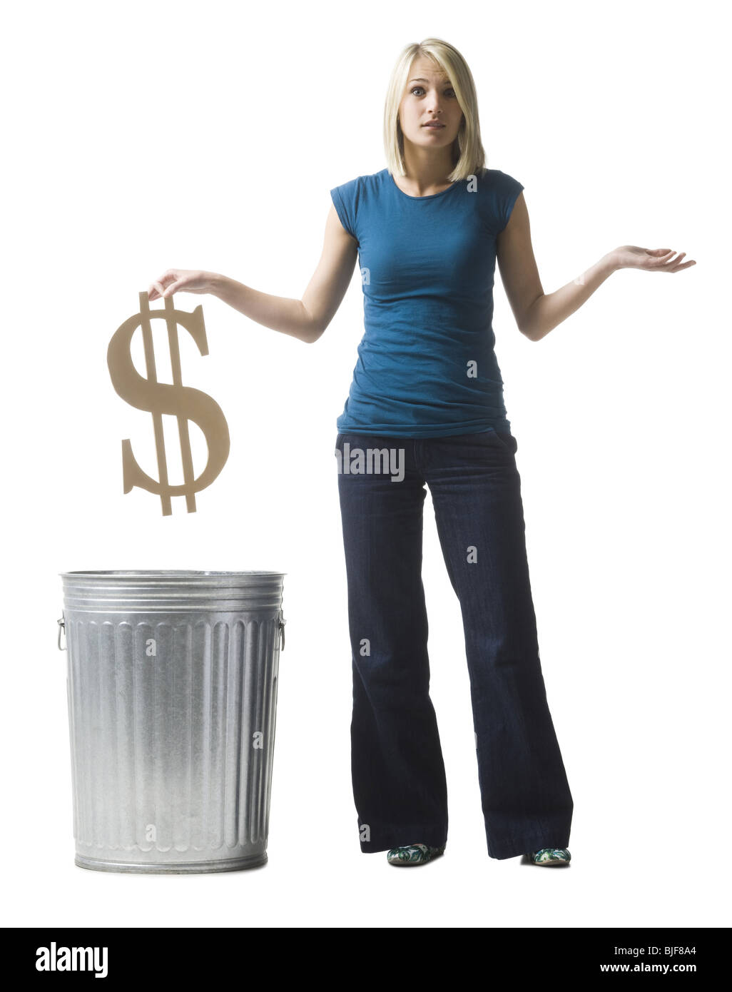 woman throwing dollar symbol in the trash - Stock Image