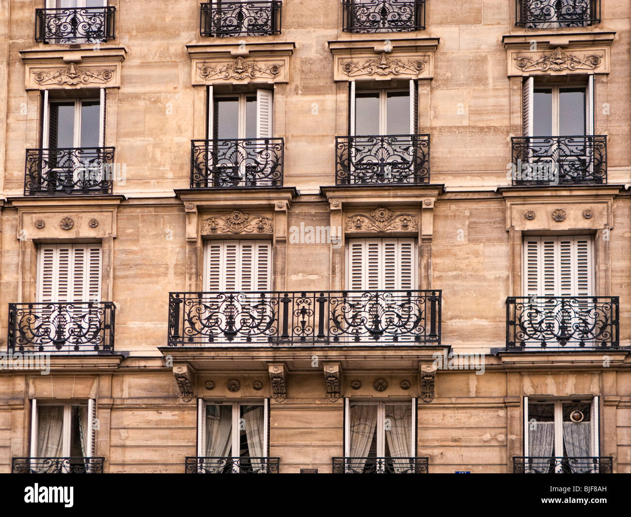 Ornate apartment block exterior with balcony in Paris, France, Europe - Stock Image