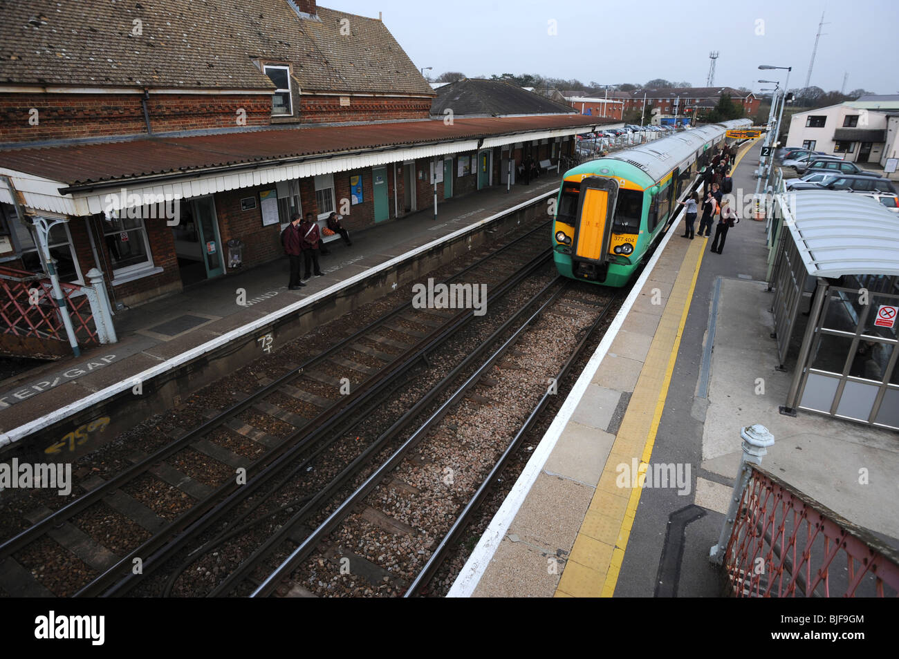 Train arrives on the platform of billingshurst a small station in west sussex - Stock Image