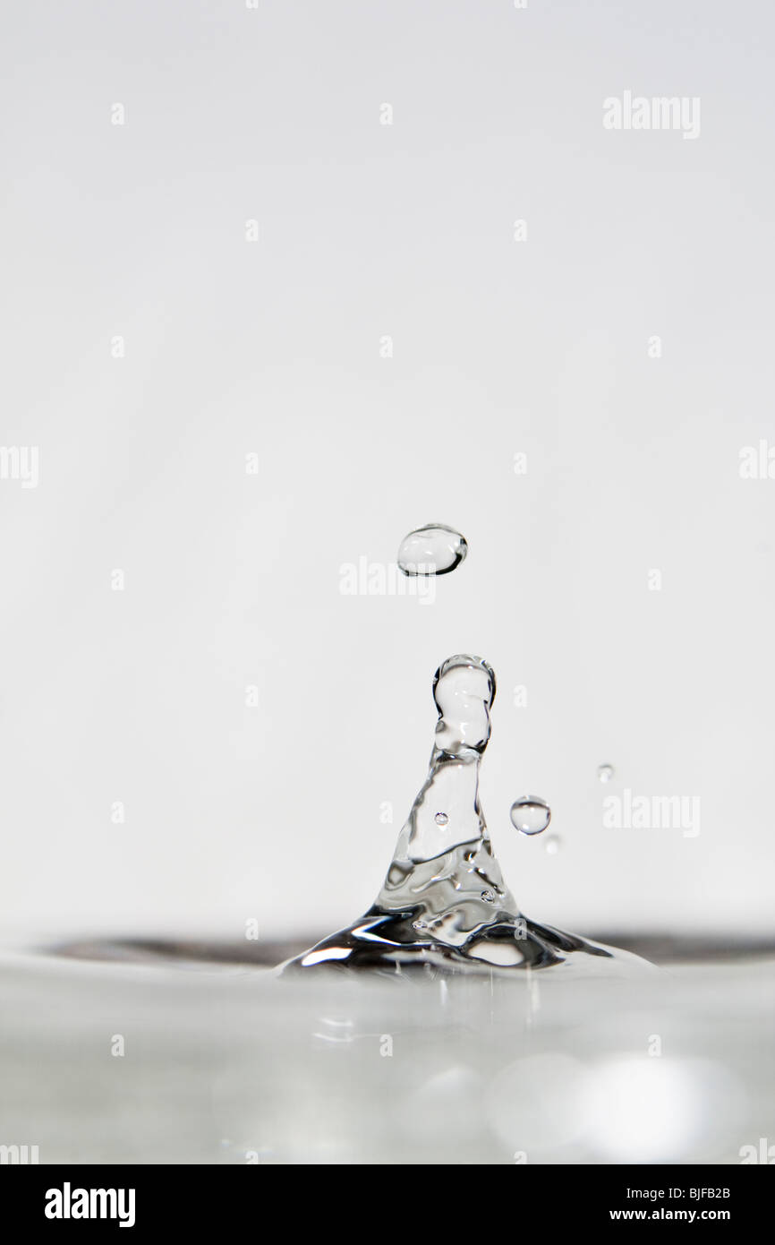 High speed photograph of a water droplet bouncing off a flat water surface. - Stock Image