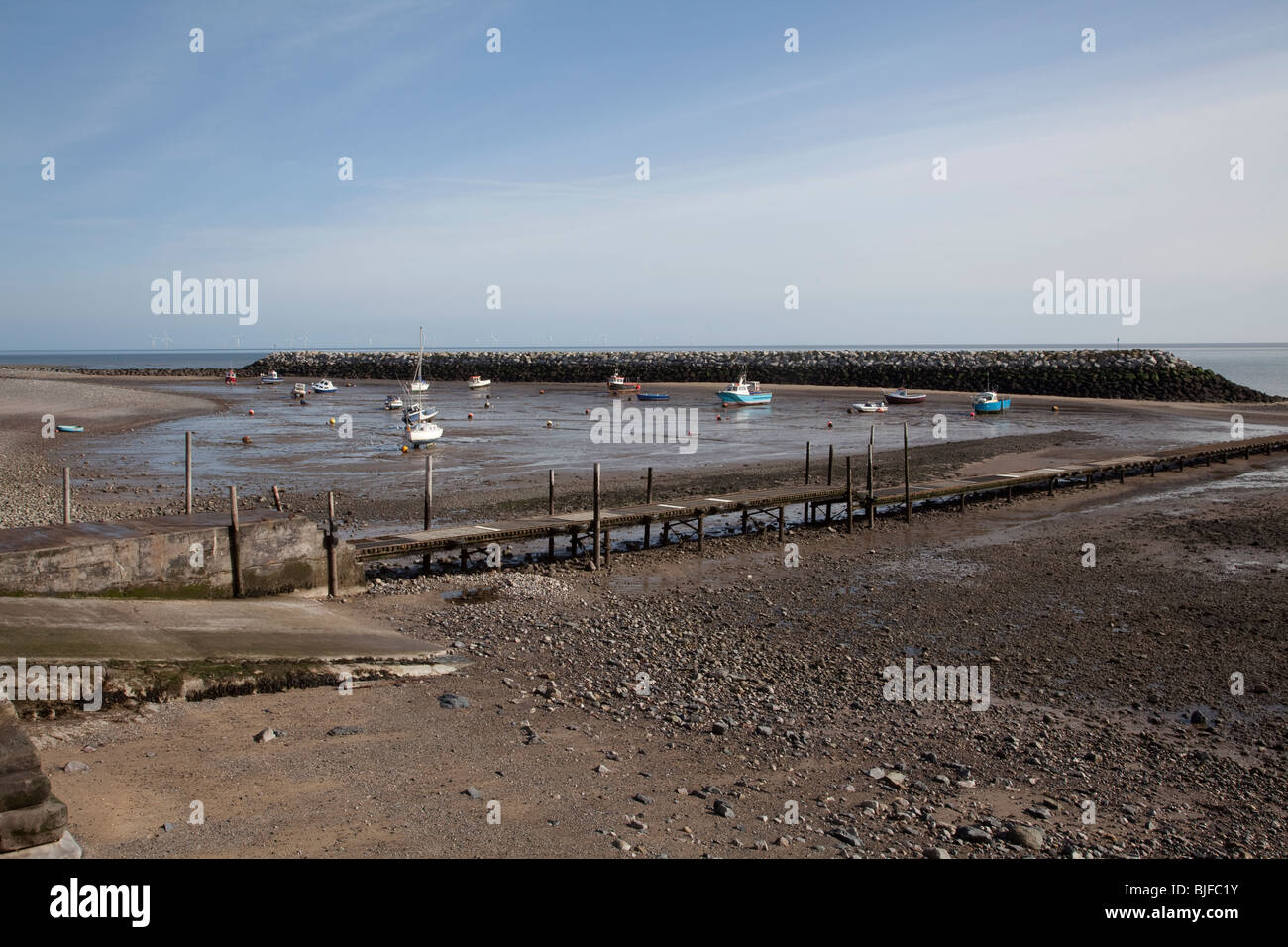 Man made harbour with small boats during low tide at Rhos on Sea holiday resort North Wales, Britain - Stock Image