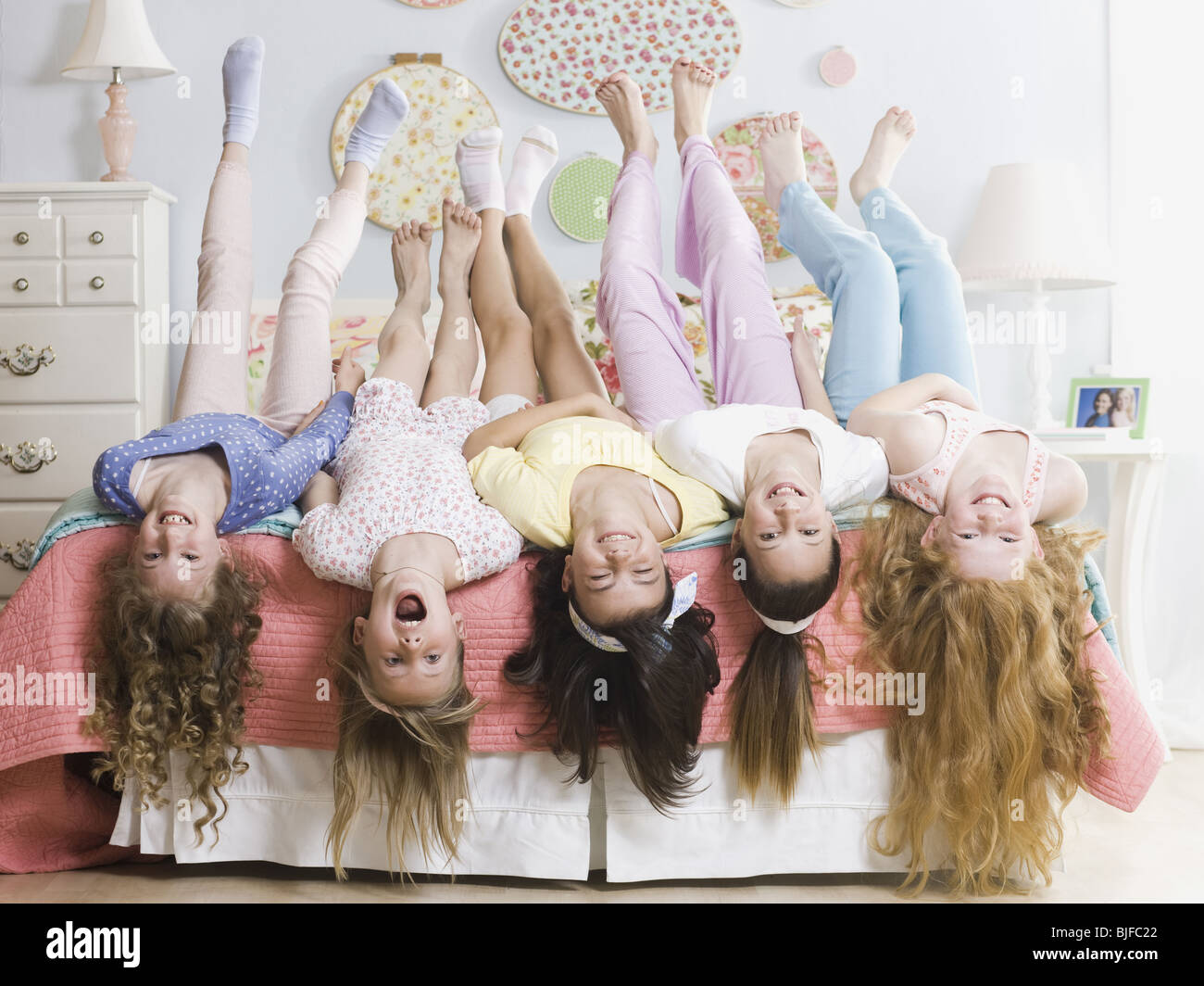 five girls on a bed upside down - Stock Image
