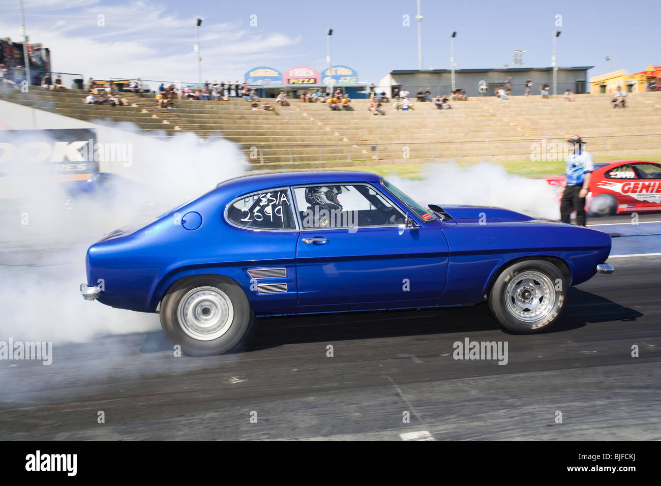 Ford Capri drag racing car performing a tire smoking burnout at the Perth Motorplex drag racing venue in Western - Stock Image