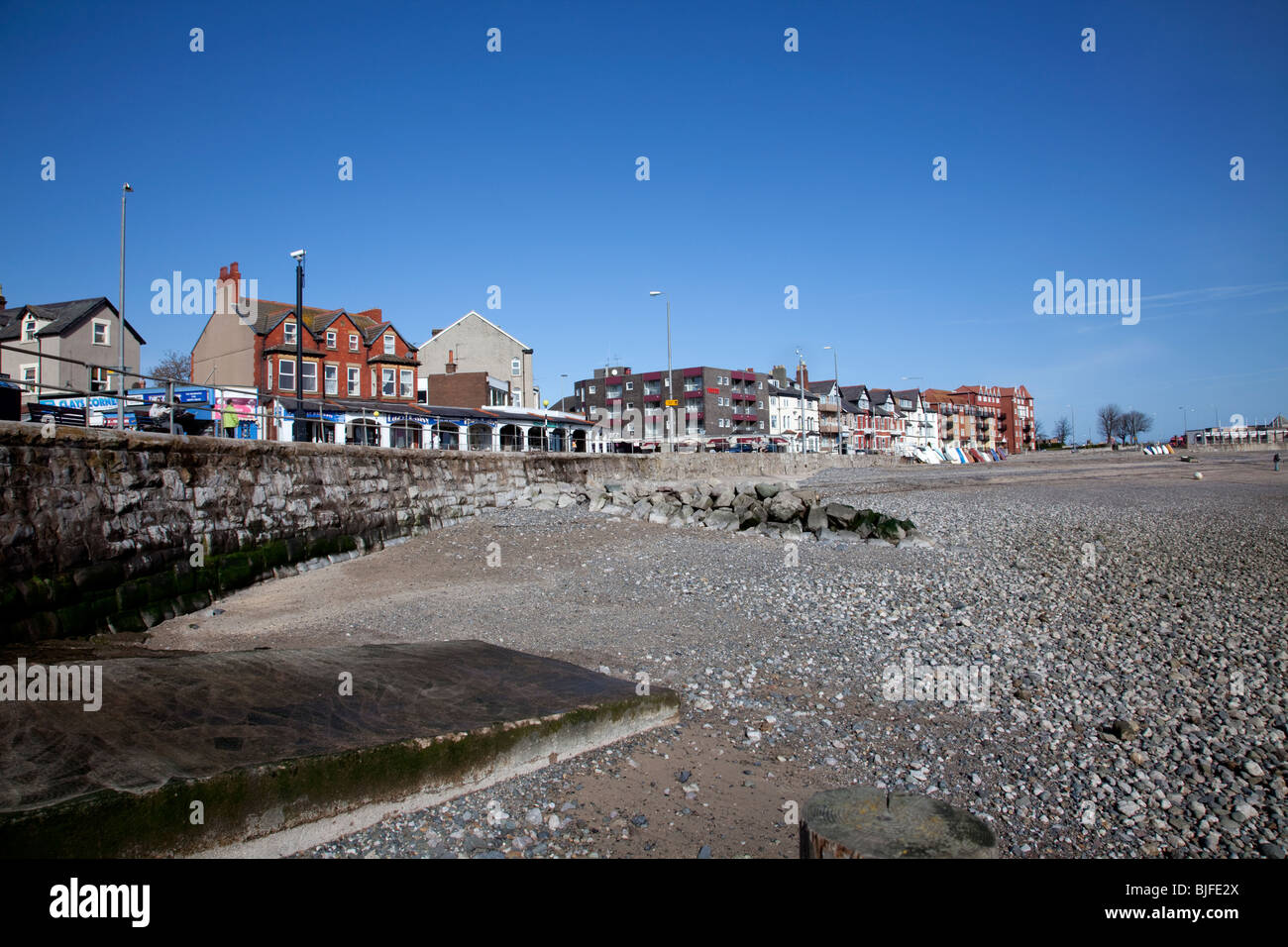 Rhos on Sea, North Wales seafront shops and accommodation viewed from the beach within a rocky breakwater Stock Photo