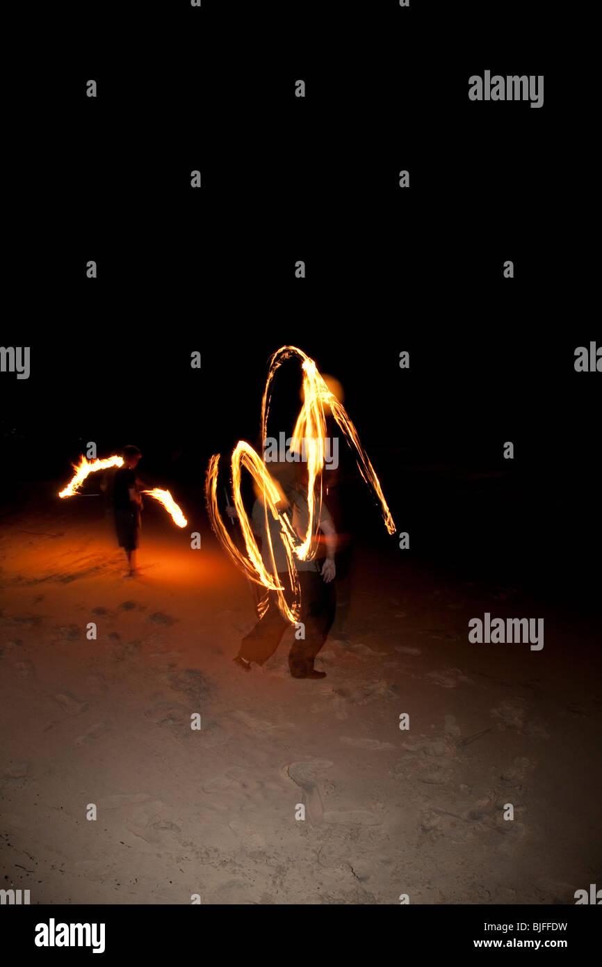 FIRE TWIRLING ON MOOLOOLABA BEACH - Stock Image