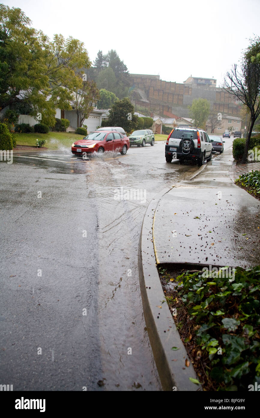Heavy rains flow down streets into Street Gutters and Storm Drains, Culver City, Los Angeles, California, USA - Stock Image