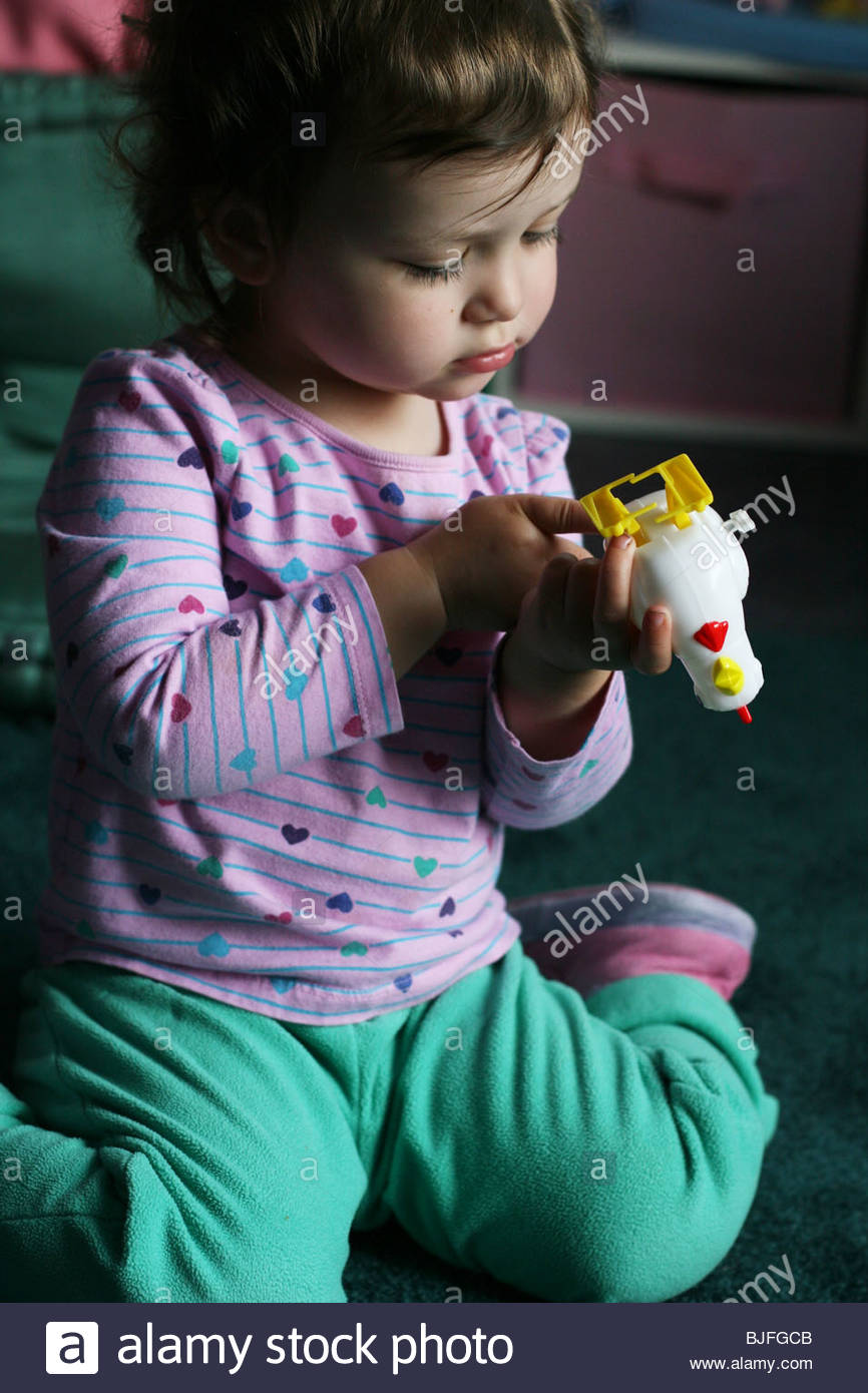 A 2 year old girl playing with a wind up chicken toy. - Stock Image