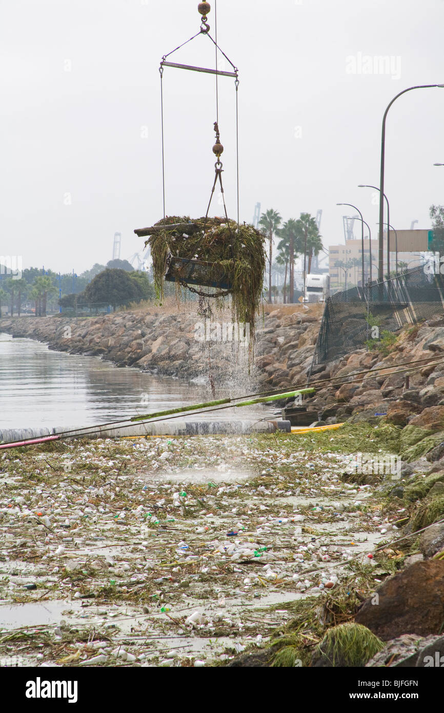 Cranes picking up garbage debris after first rain of the season from Garbage boom on the Los Angeles River in Long - Stock Image