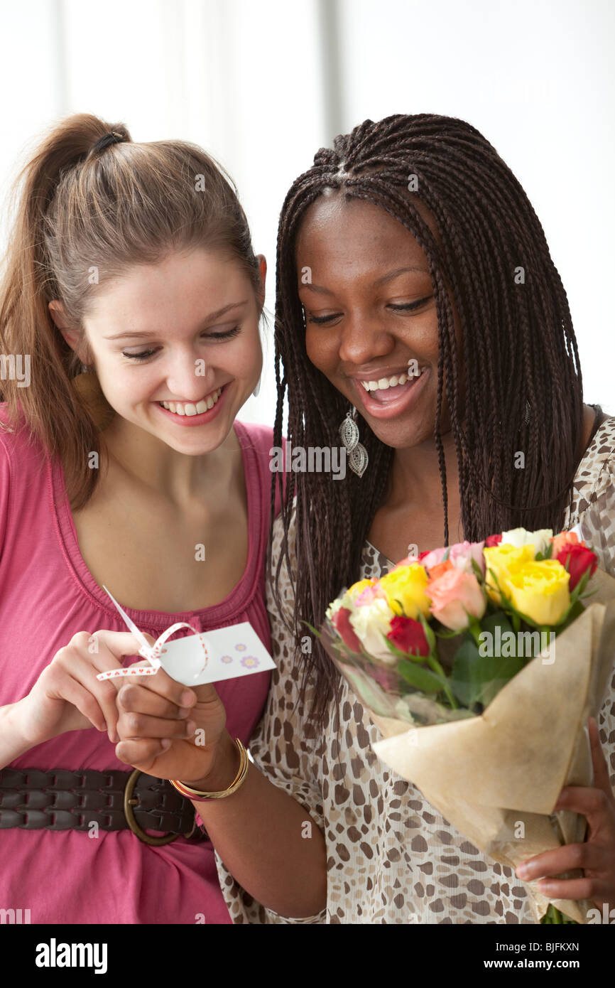 Teenage girls wondering who send them a bouquet of flowers - Stock Image