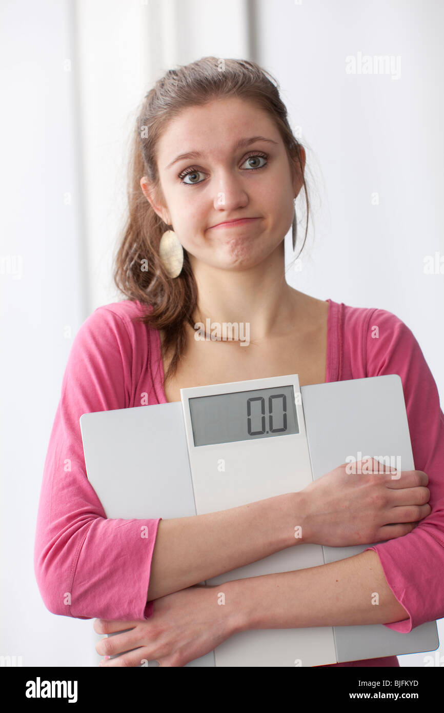 Teenage girl carryiong a scale and wondering about her weight - Stock Image