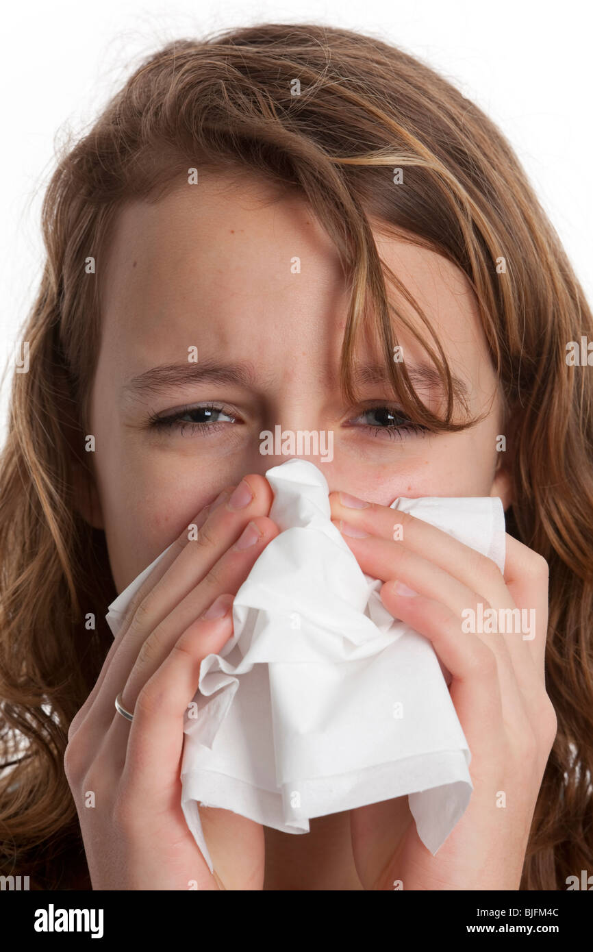 Teenage girl blowing her nose in a paper handkerchief - Stock Image