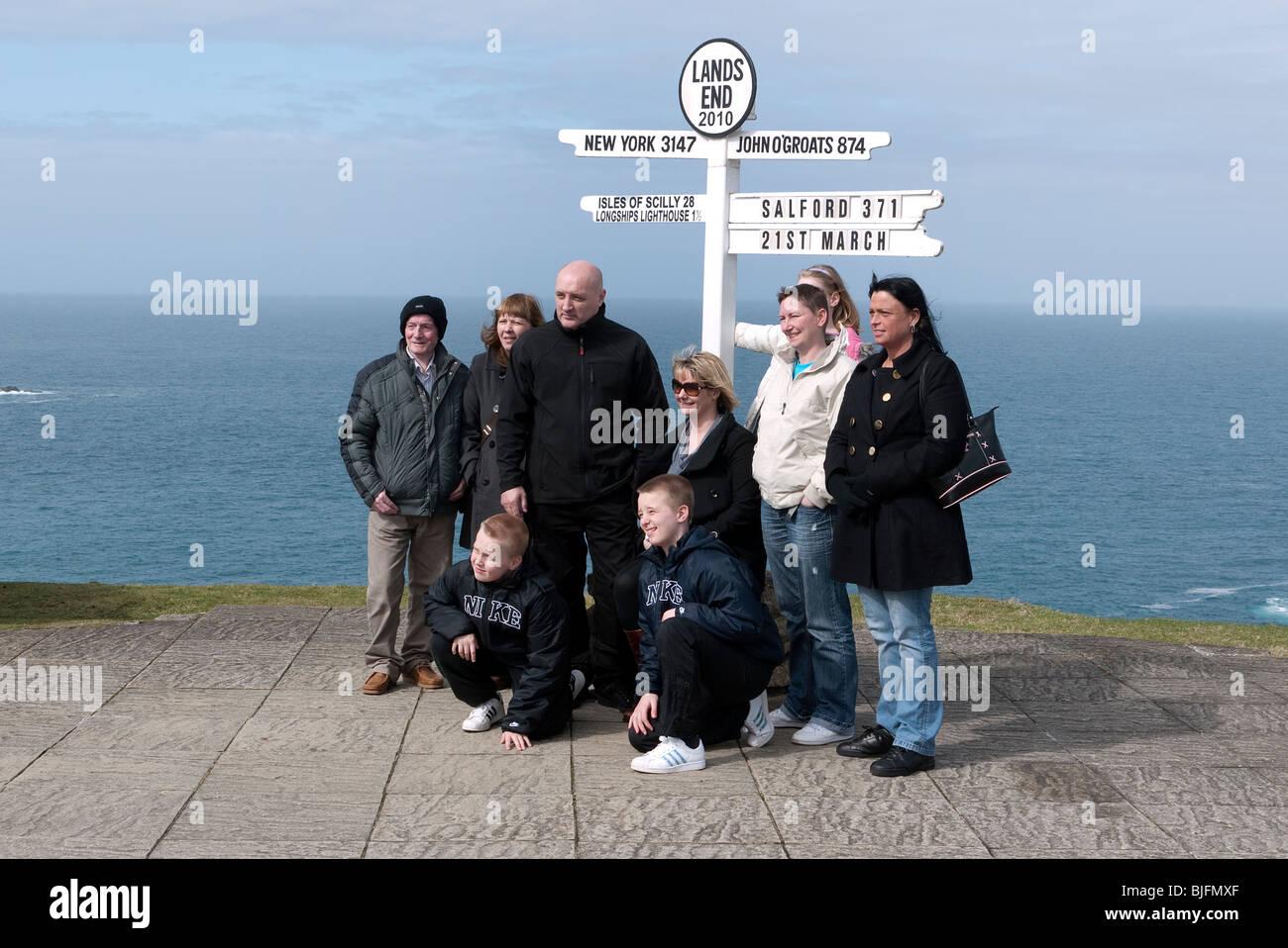 Family at Land's End signpost Cornwall UK - Stock Image
