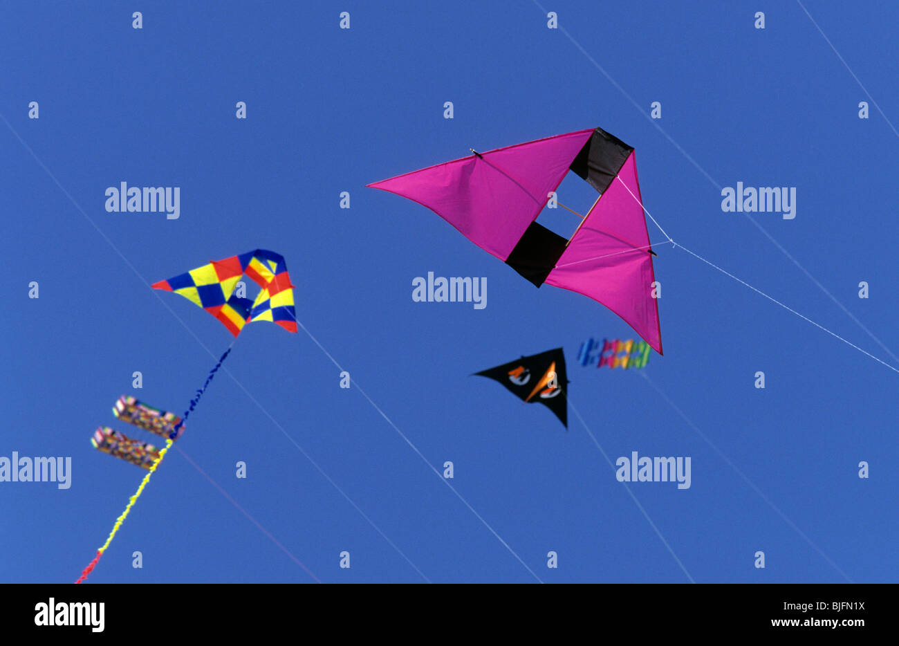 Colourful figure kites flying high in sky - Stock Image