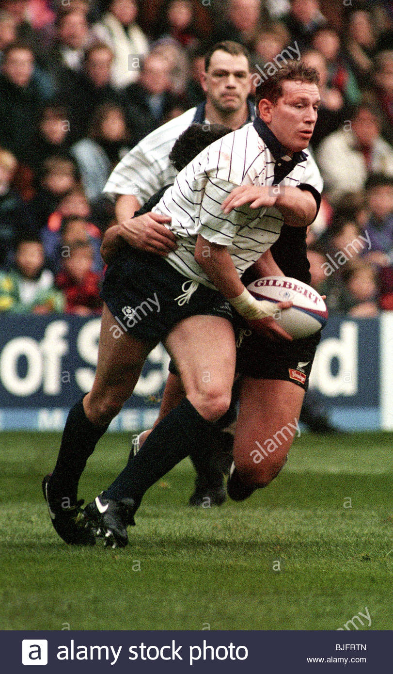 20/11/93 SCOTLAND V NEW ZEALAND (15-51) MURRAYFIELD - EDINBURGH Scotland's Andy Nicol passes the ball as a tackle - Stock Image