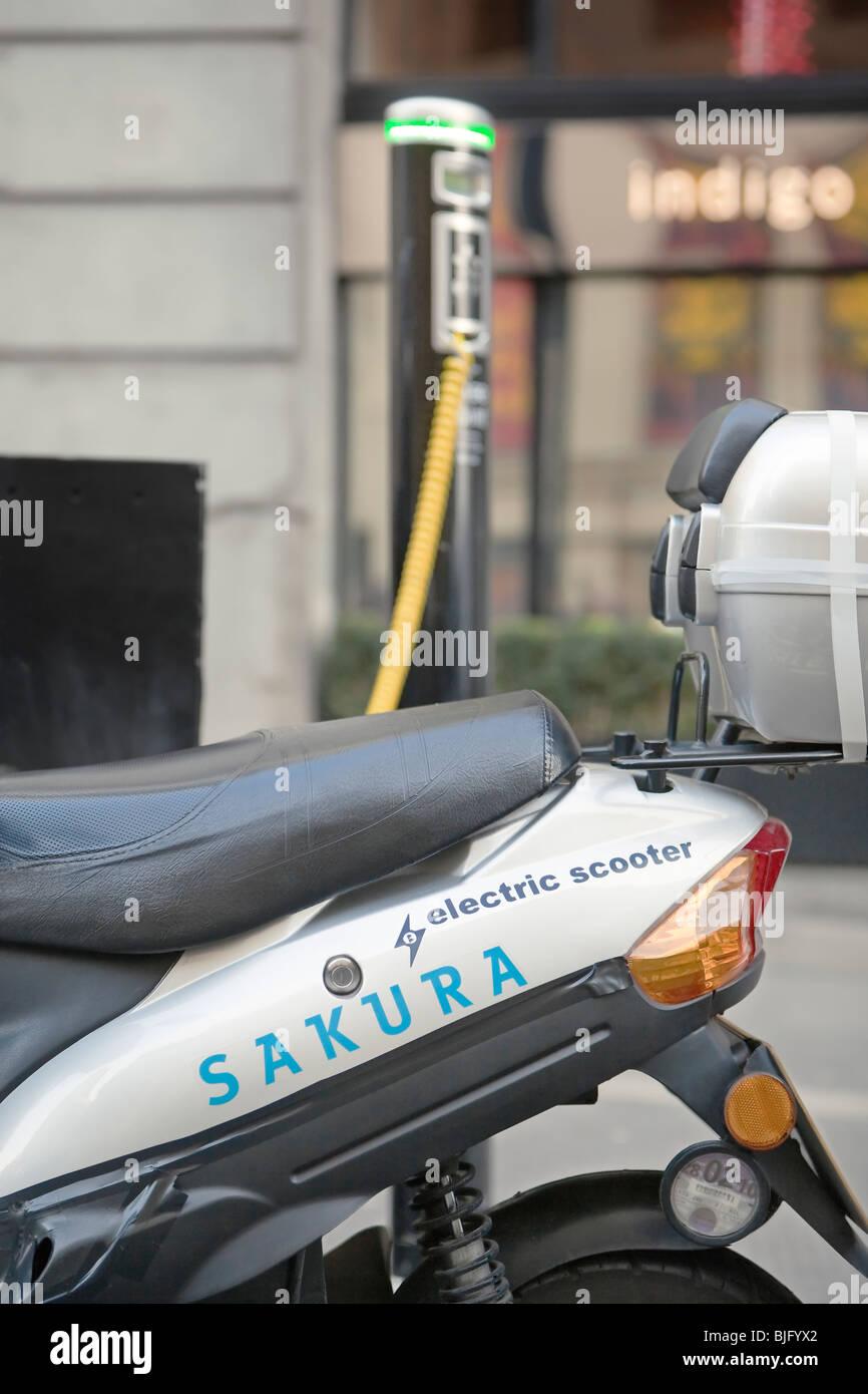 An electric motorbike recharging at an electrobay, London , UK. - Stock Image