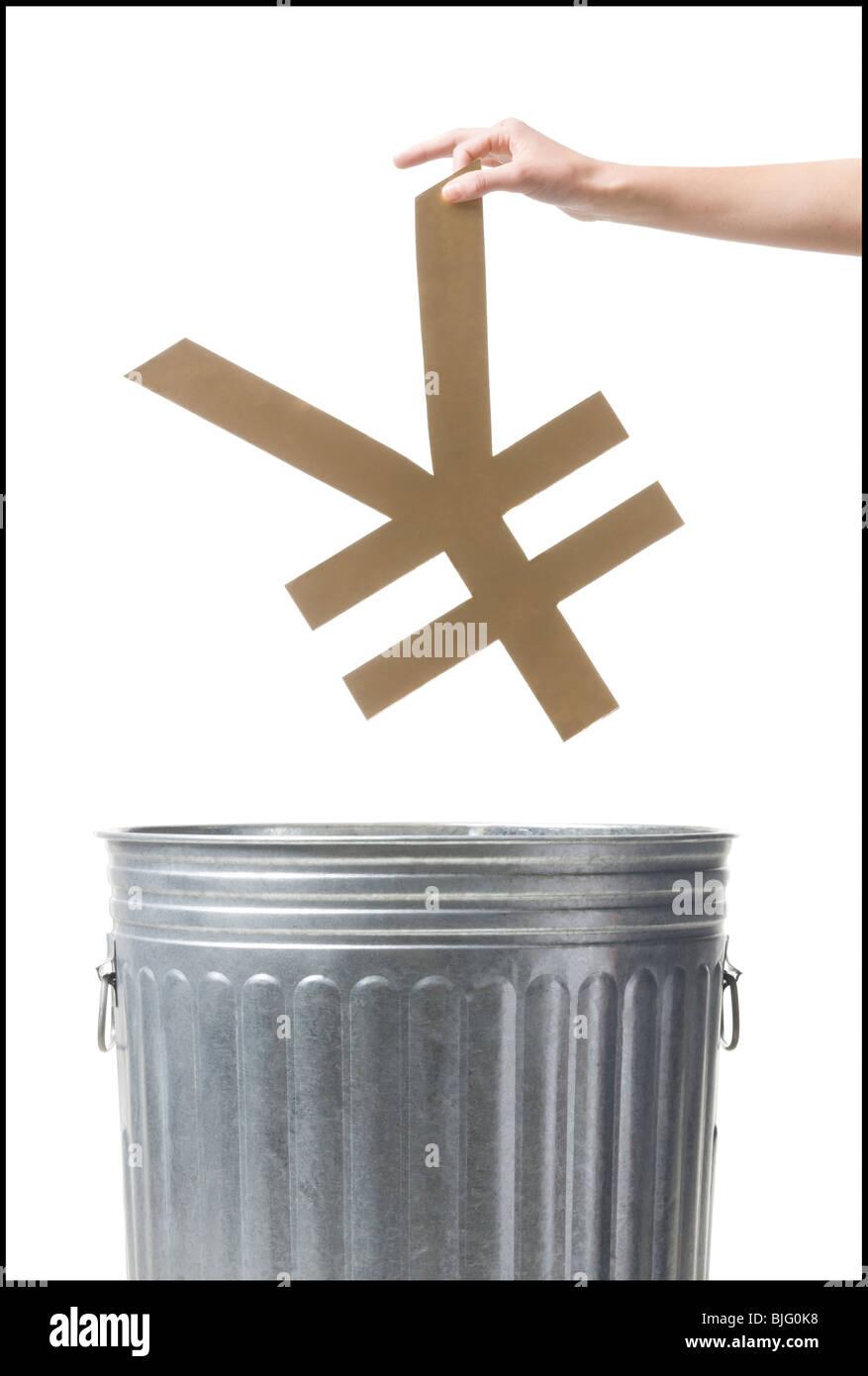 throwing yen symbol in the trash - Stock Image