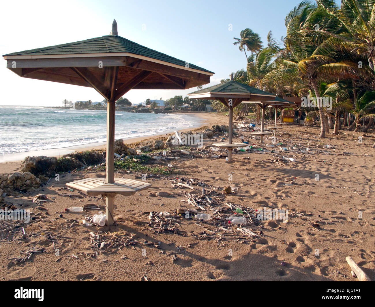 A setting sun on a rubbish strewn Caribbean beach with deserted shady tables empty plastic bottles and wind blown - Stock Image