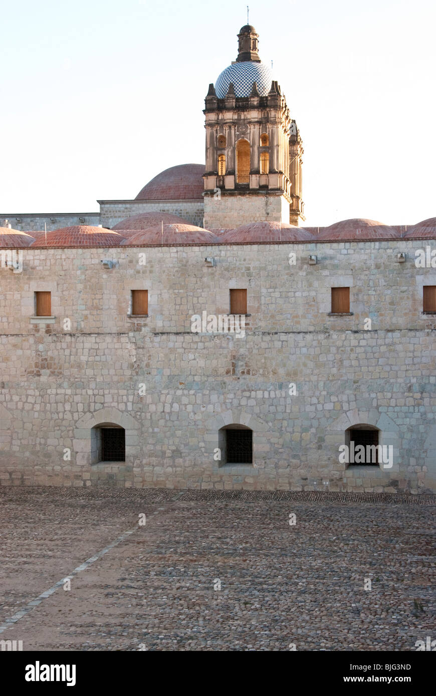 view across former monastery courtyard to bell towers of Santo Domingo Church in late afternoon light Oaxaca City - Stock Image