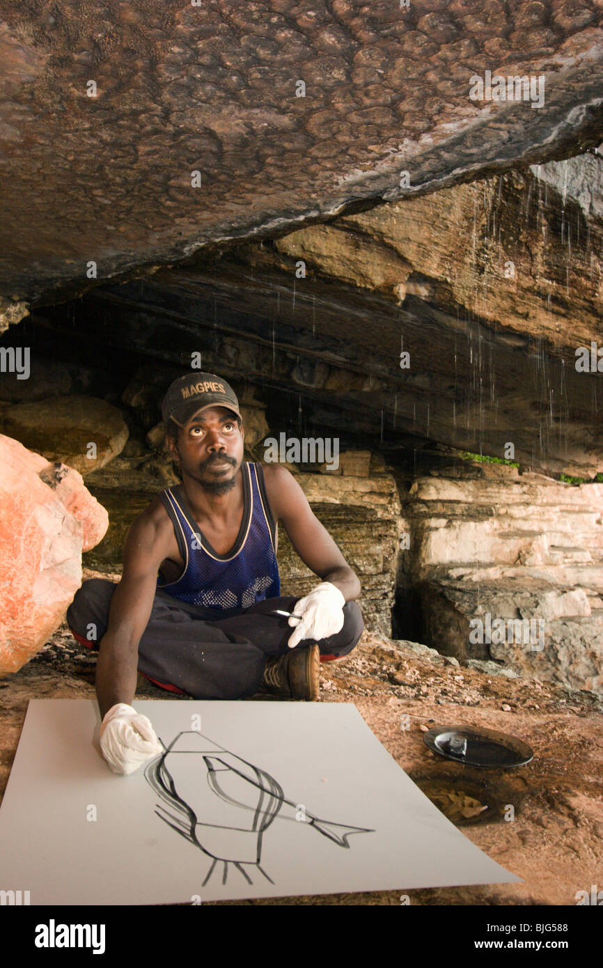 Aboriginal artist Terence Nabegeyo etching a lithograph in a cave in the rain on Injalak Hill Eastern Arnhem Land - Stock Image