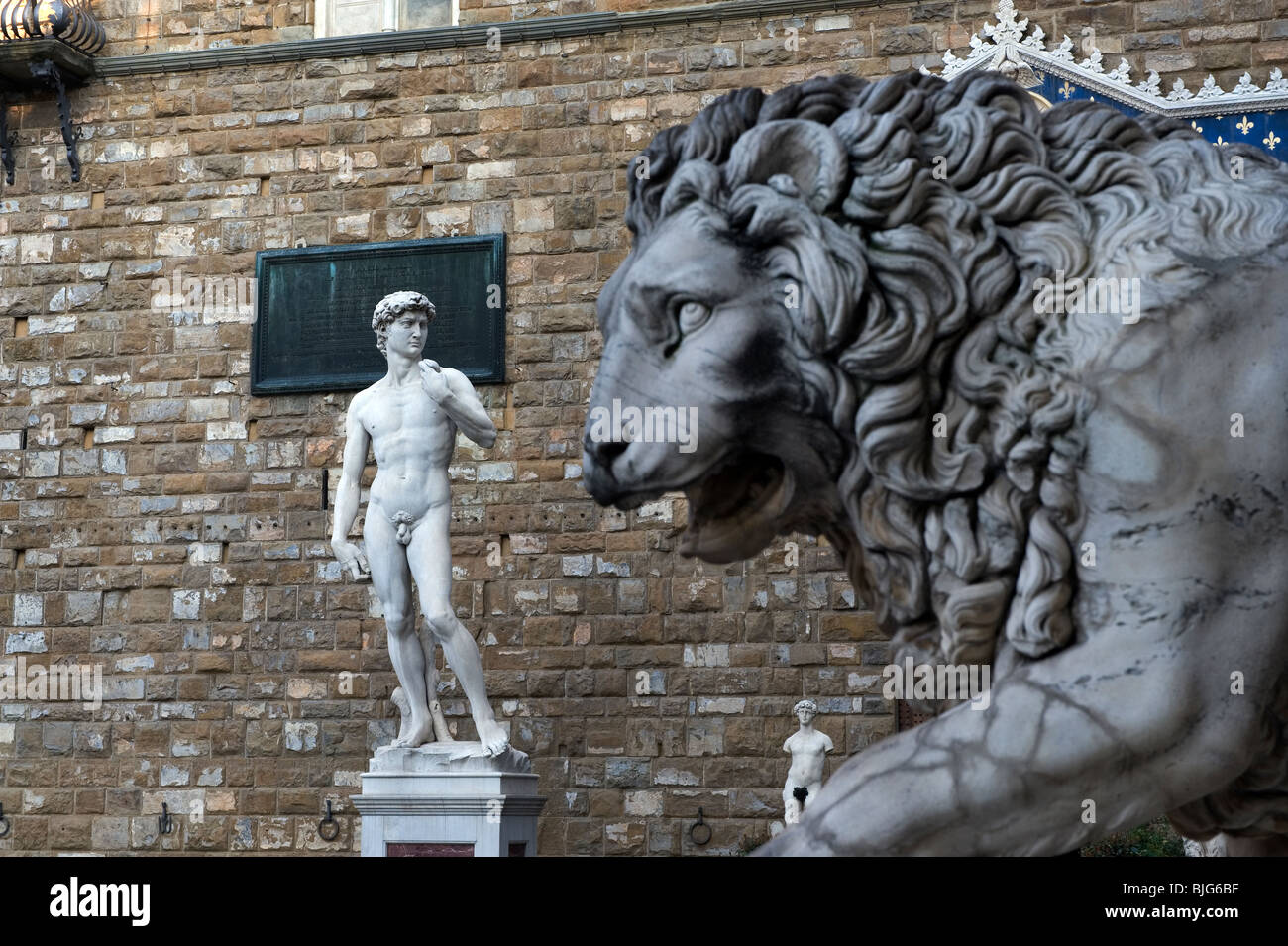 Florence,Tuscany,Italy. Statues of David by Michelangelo ( copy ) on left and the Flaminio Vaca-Lion in the Loggia - Stock Image
