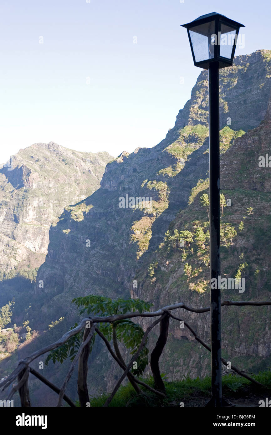 A lamp stands by a crooked fence over the Valley of the Nuns on the island of Madeira, Portugal. - Stock Image