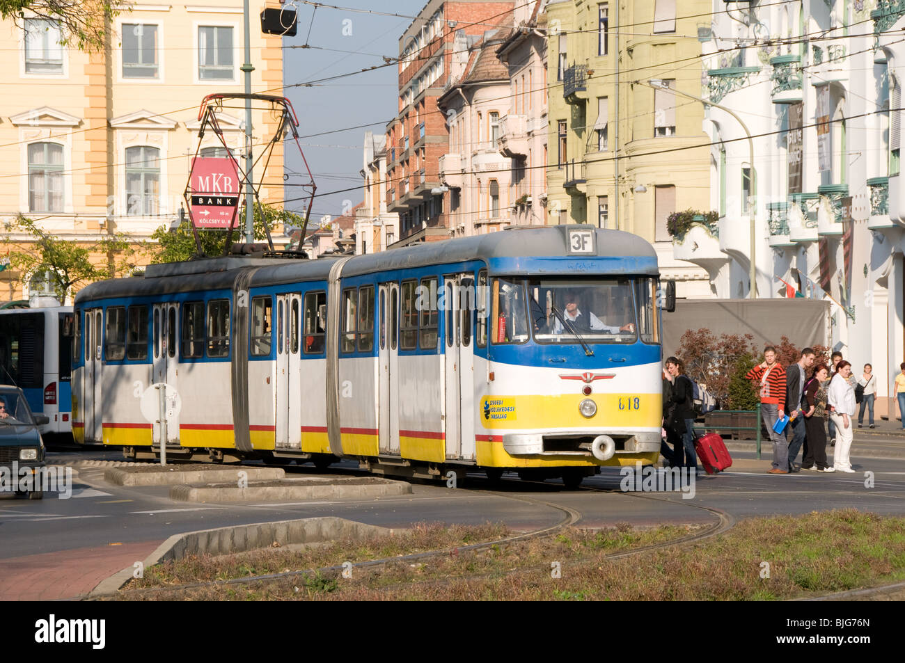 A three section articulated tram picks up passengers in Szeged, Hungary Stock Photo