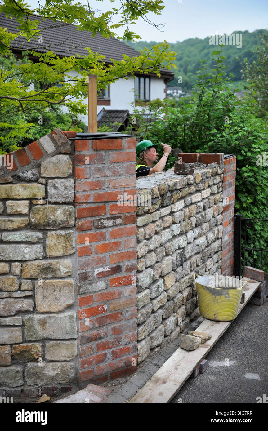 Building a garden wall with cotswold stone and cement mortar with reclaimed red brick pillars and coping UK - Stock Image
