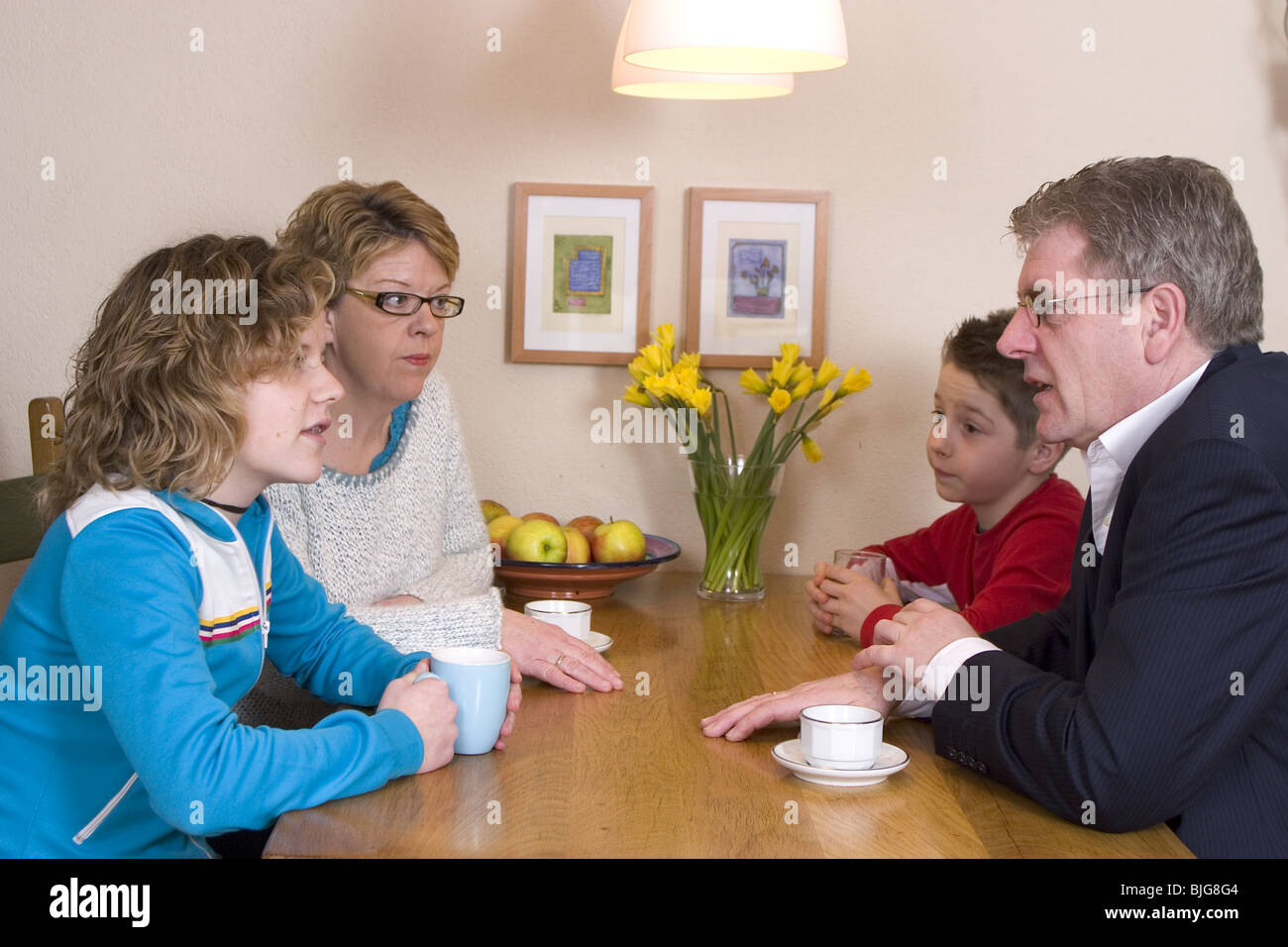 Teenagers talking with adults, do conversation starter, family conflict at family meeting at table at home, family - Stock Image
