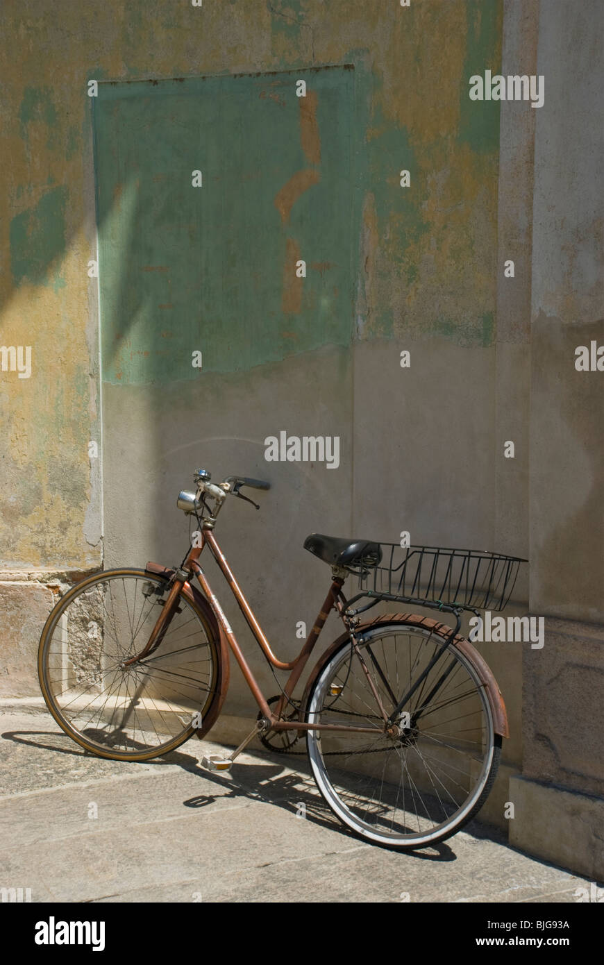 Old style bicycle leaning on colored wall - Stock Image