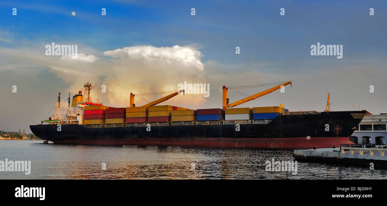 Panoramic view of container cargo ship docked in Havana bay at sunset - Stock Image