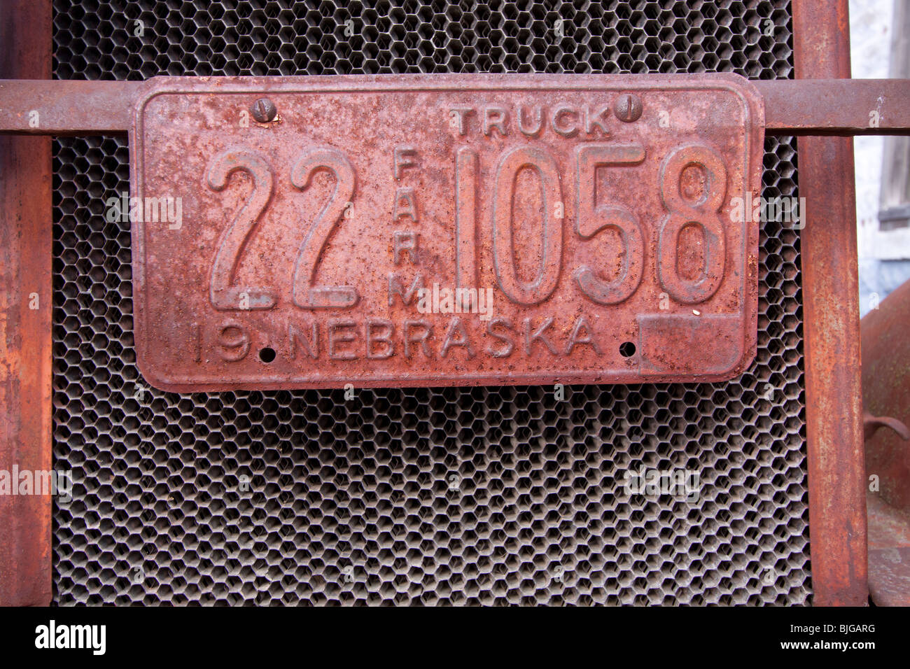 A rusted farm license plate on a rusting out antique car in Nebraska, USA. - Stock Image