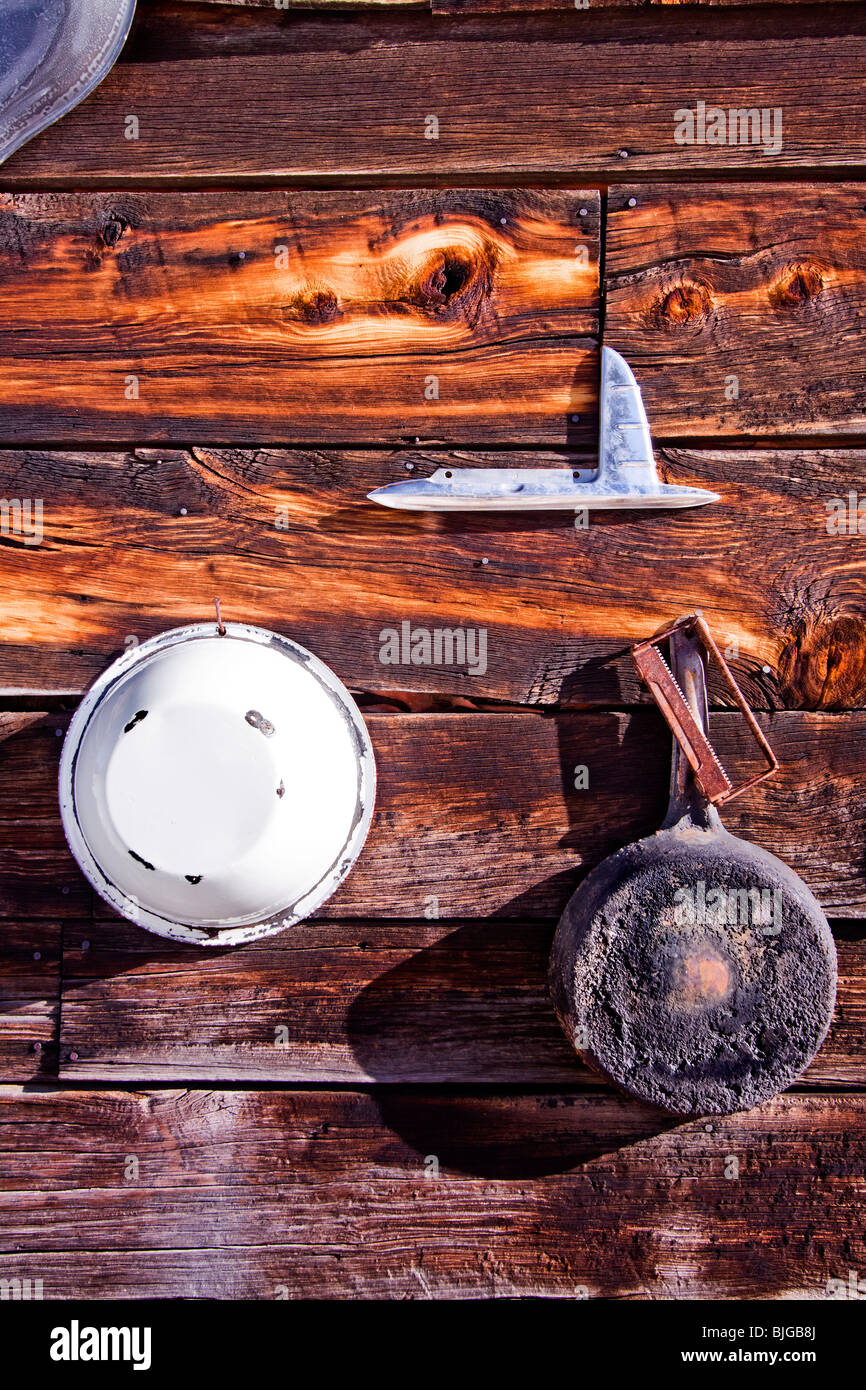 Pots, pans, and assorted tools hang on the exterior wall of a wood cabin in Guffey, Colorado, USA. - Stock Image