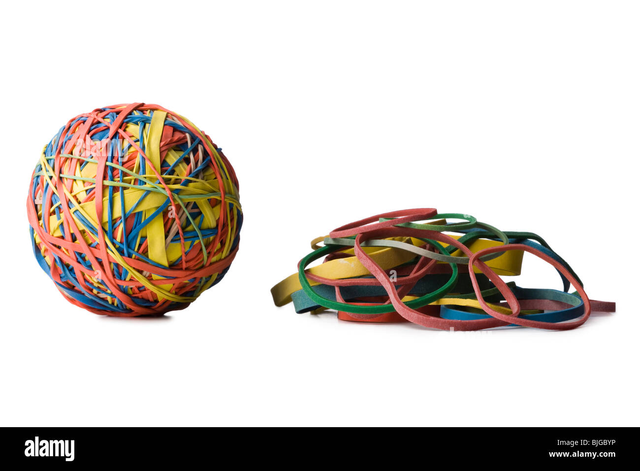 rubber band ball next to a pile of rubber bands - Stock Image