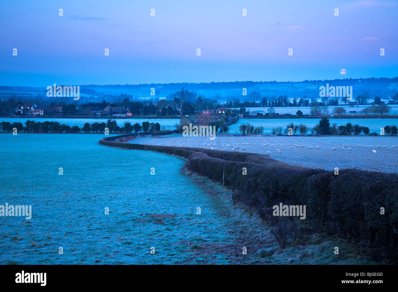 The moon sets as dawn arrives over the Chiltern Hills near Hambleden village looking towards Mill End and the River - Stock Image