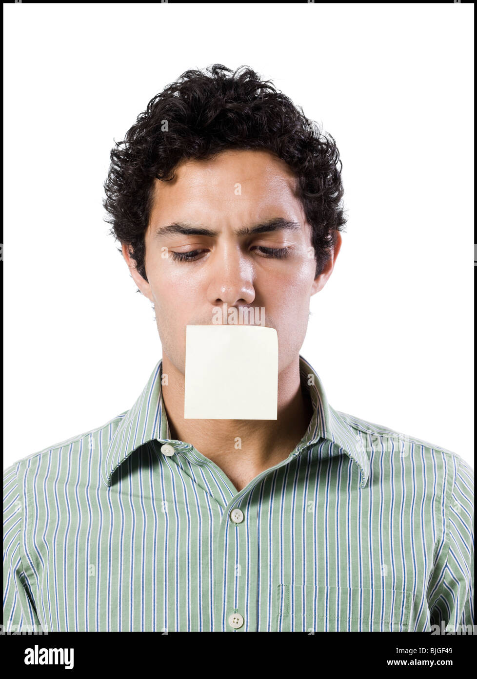 man with a post it note over his mouth - Stock Image