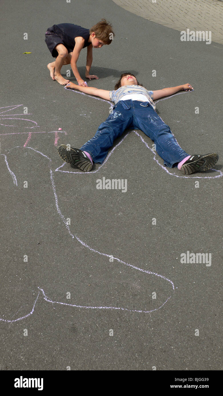 Boy chalk-drawing the outline of his friend in a street, Werl, Germany Stock Photo