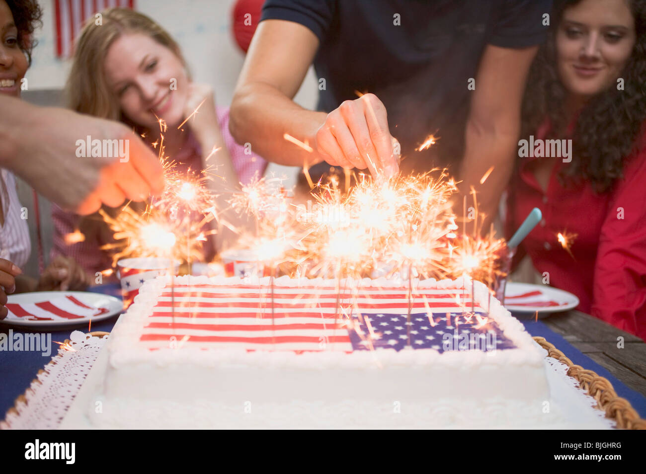 Hands lighting sparklers on a cake (4th of July, USA) - - Stock Image