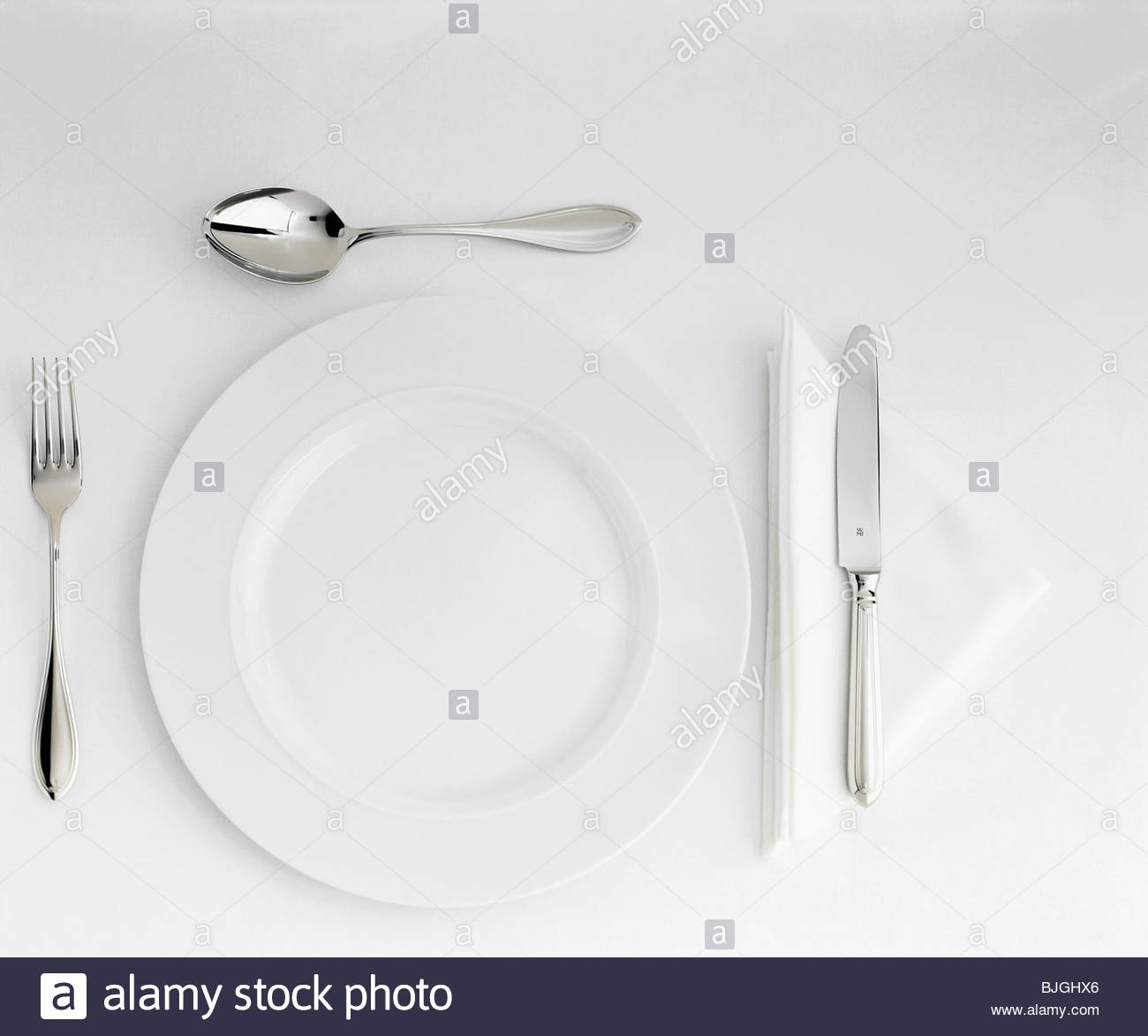 Table Setting with White Plate, Cutlery & Triangular Napkin Stock ...