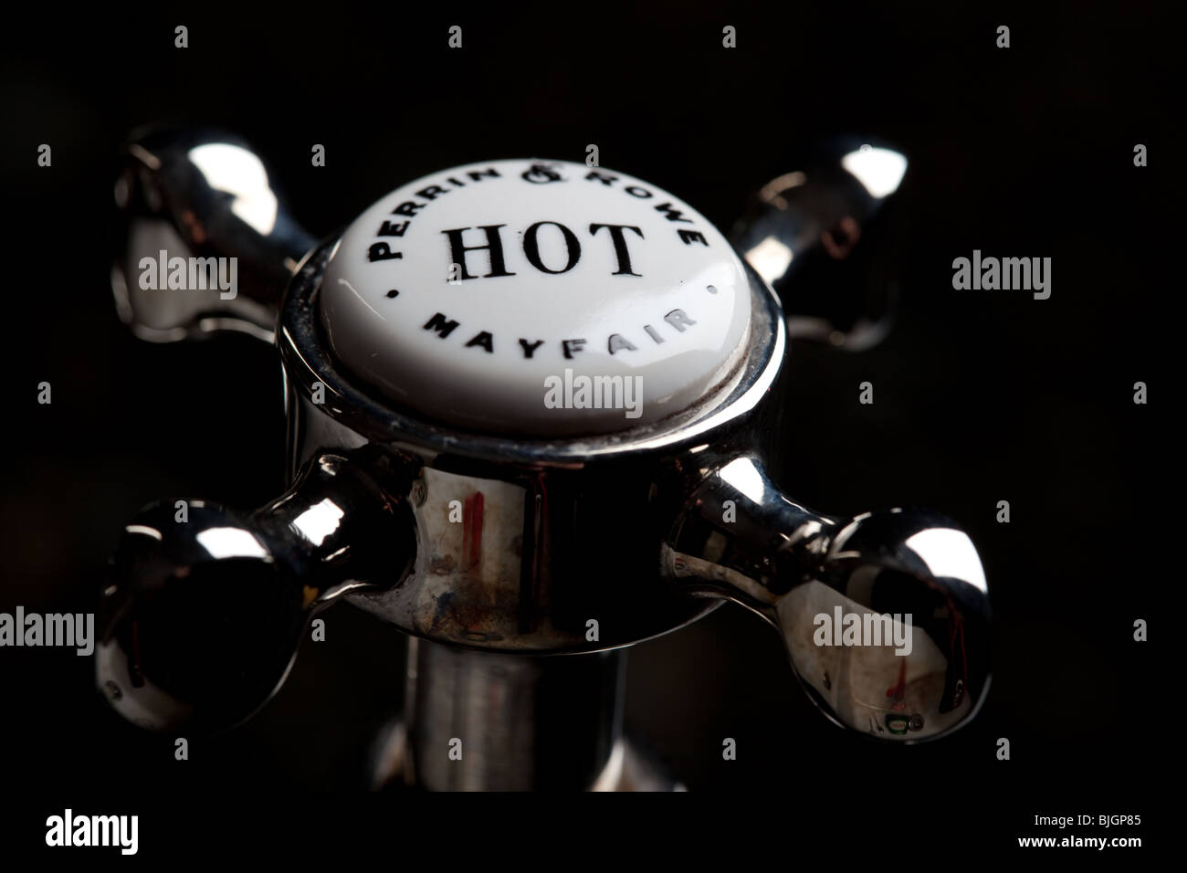 A sightly grubby and tarnished hot water tap - Stock Image