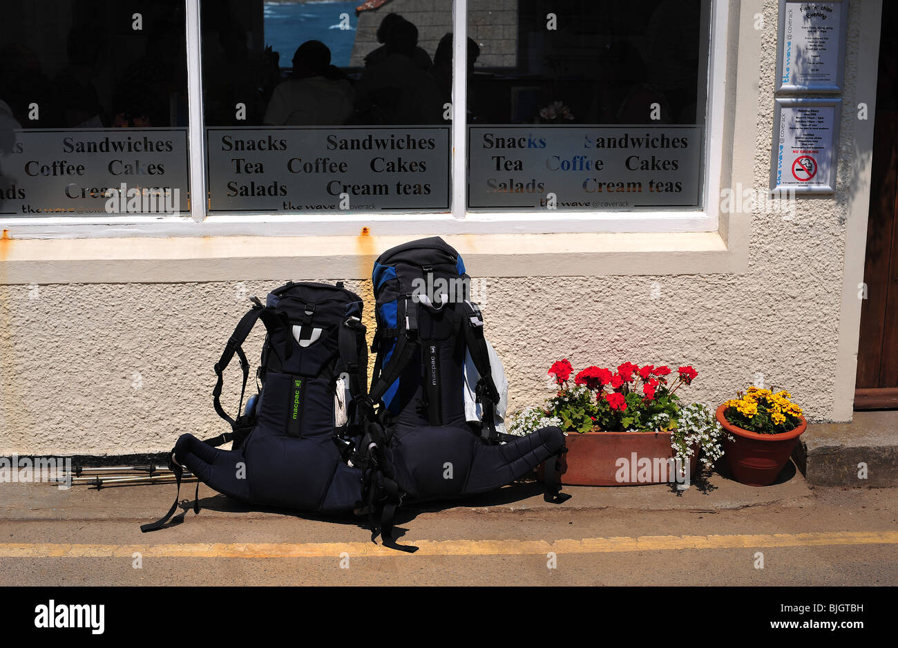 two back pack ruck sacks left outside a cafe in Coverack, Cornwall, UK - Stock Image