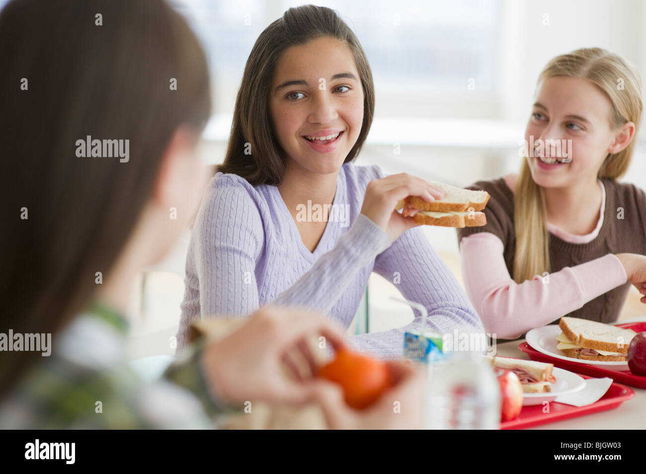 Friends eating in cafeteria - Stock Image