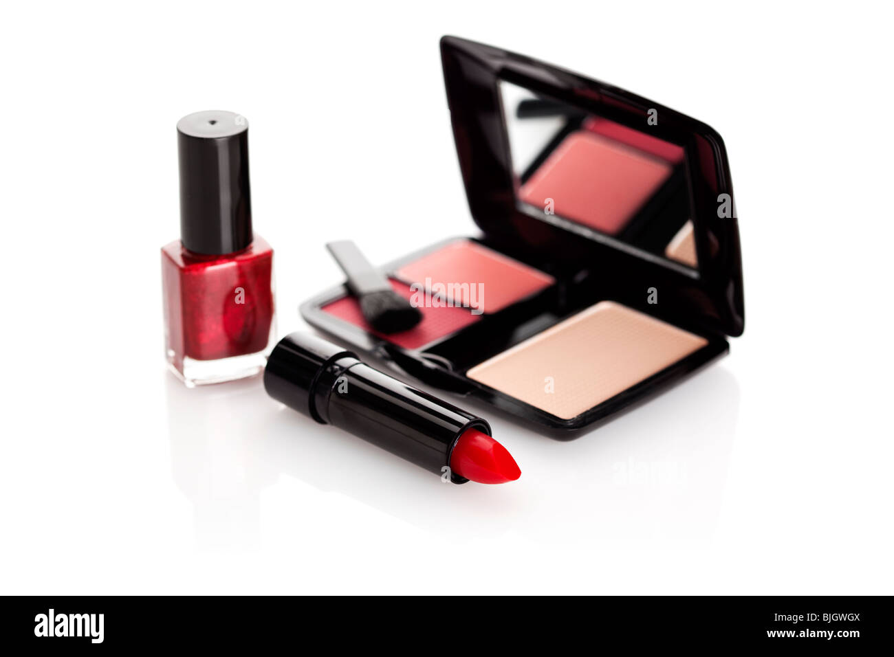 red lipstick, nail varnish and case with rouge and make up on white background - Stock Image